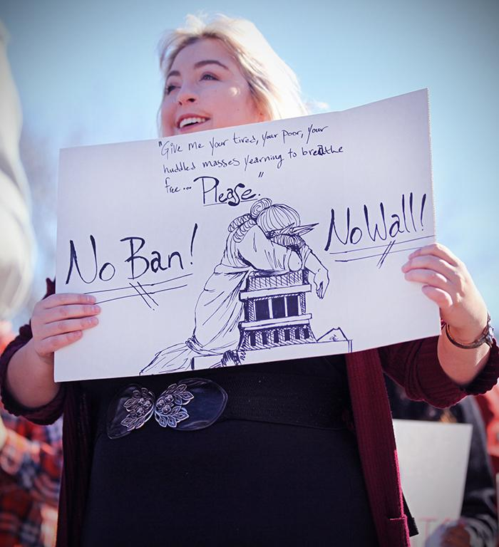 Emily Schackleford, marketing senior, holds up her creative sign, at the rally against the immigration executive order, on Feb. 1st. Photo by Bridget Reilly