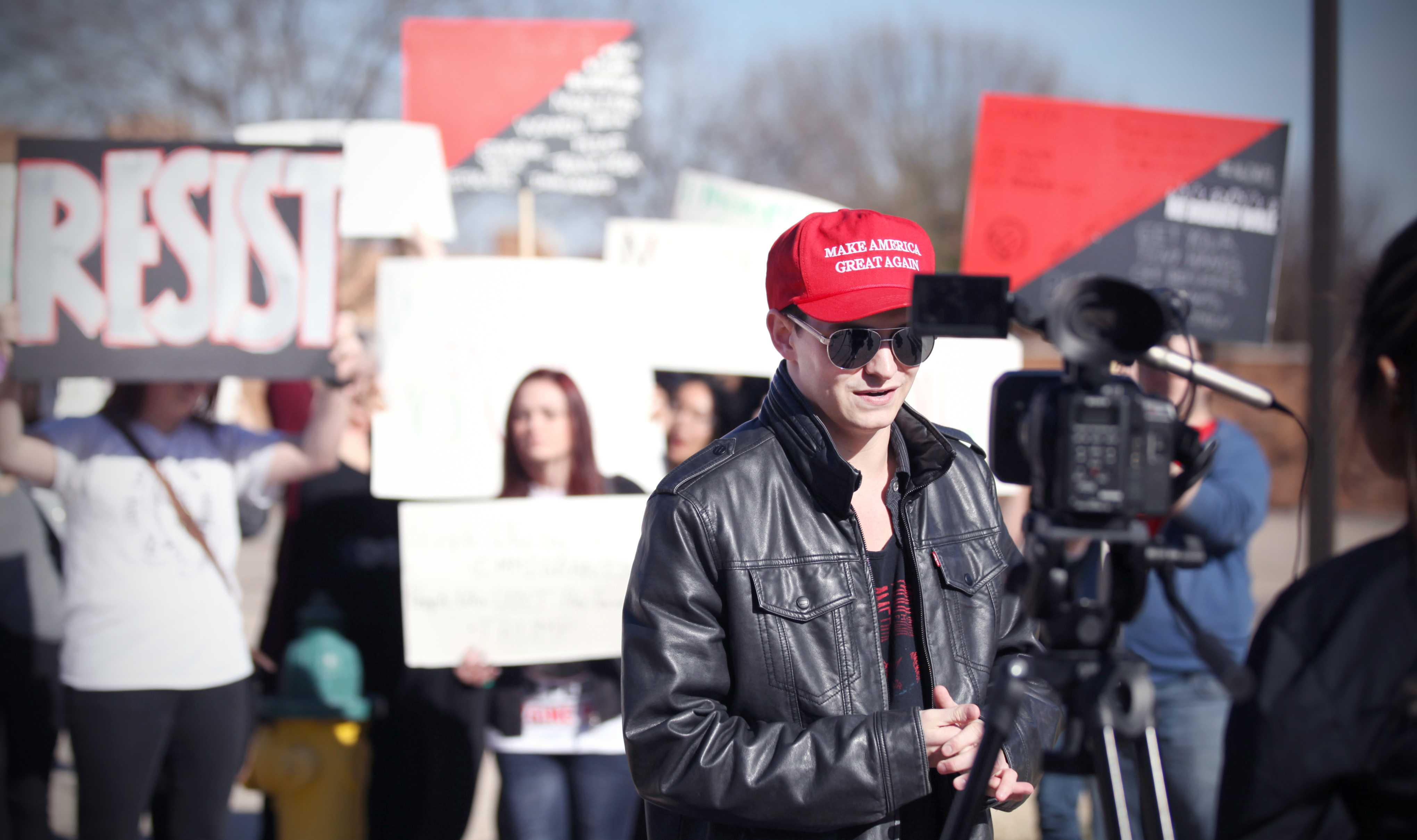 Brady Burross, mechanical engineering senior, speaking to the student media about why he thinks the immigration executive order is a good idea. In the background are ralliers silently protesting. The rally against the immigration executive order, on Feb. 1st. Photo by Bridget Reilly