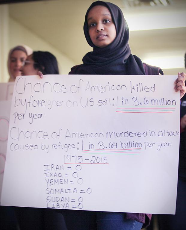 Asma Mohammed, radiology freshman, holds a poster of statistics, at the rally against the immigration executive order, on Feb. 1st. Photo by Bridget Reilly