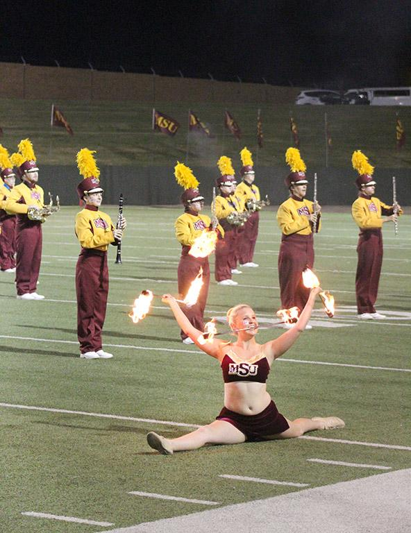 Alexis Maggard, spech education freshman, ends her routine in the splits with three lit batons during the Mustangs vs Western New Mexico football game held in the Wichita Falls Memorial Stadium. Sept. 30. Photo by Marissa Daley
