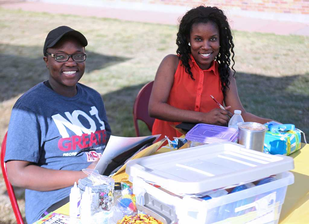 """Mercy Riaro and Akeida Alexis, 2017 graduates, make the outlines for their graduation cap designs at the spring Finals Frenzy on the Jesse Rodgers Promanade on May 4, 2017. """"Finals Frenzy is my favorite event at the university, they provided lots of materials to work with, so we are just having fun designing,"""" Alexis said. Photo by Timothy Jones"""