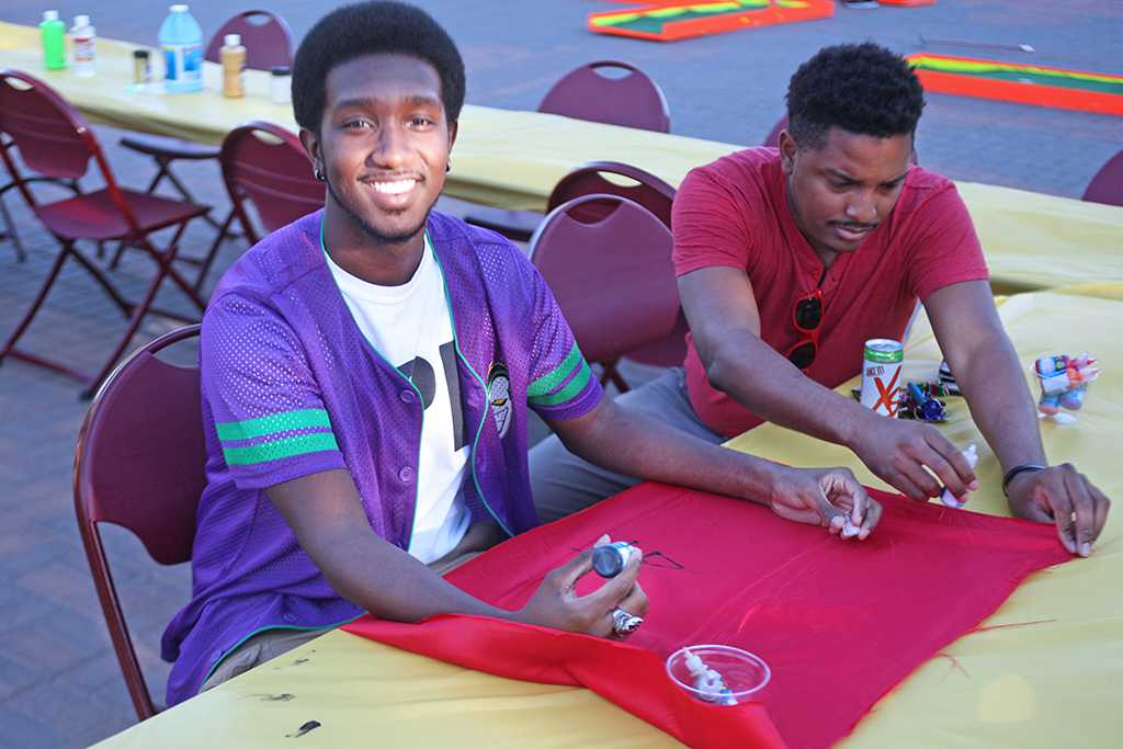 """D'Aaron Clayton, pre-dental senior, and Kyle Gordon, mechanical engineering senior, paint super-hero capes to be donated to the Children's Hospital at the spring Finals Frenzy on the Jesse Rodgers Promanade on May 4, 2017. """"Every year we do this at the Finals Frenzy, we always try to give back to kids, the military and the needy.This year we are making super-hero capes that we are going to donate to the Children's Hospital,"""" Gordon said. Photo by Timothy Jones"""