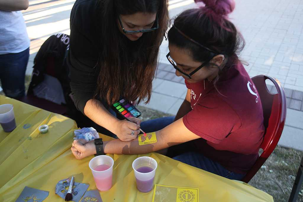 """Xochit Cruz, political science sophomore, gets a temporary tattoo at the spring Finals Frenzy on the Jesse Rodgers Promanade on May 4. """"Volunteering with my sorority sisters makes it fun, we're all just having a good time,"""" Cruz said. Photo by Timothy Jones"""