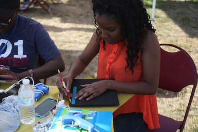 Akeida Alexis, 2017 graduate, makes the outlines for her graduation cap design at the spring Finals Frenzy on the Jesse Rodgers Promanade on May 4, 2017. Photo by Timothy Jones