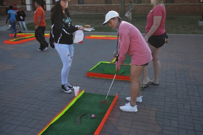 Maley Villanueva, dental hygeine sophomore, tees up on the mini golf course at the spring Finals Frenzy on the Jesse Rodgers Promanade on May 4, 2017. Photo by Timothy Jones