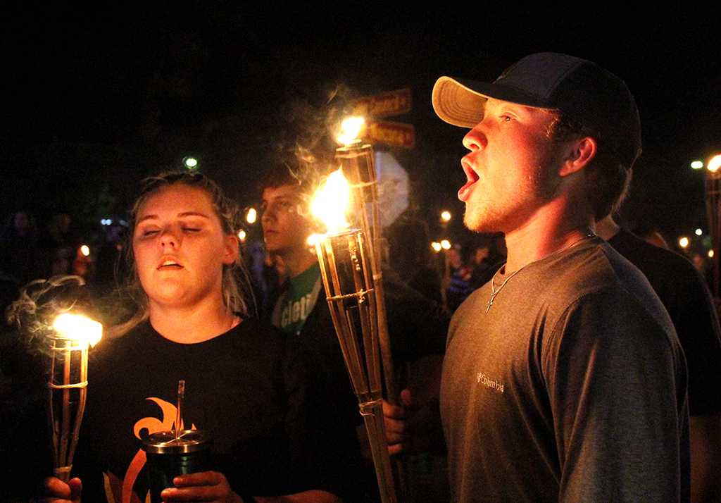 Trey Honea, Criminal Justice Sophmore, ends the torch light parade by blowing out his torch as he and his friends make their way towards the bonfire, Thursday, Oct 19,2017. Photo by Sara Keeling