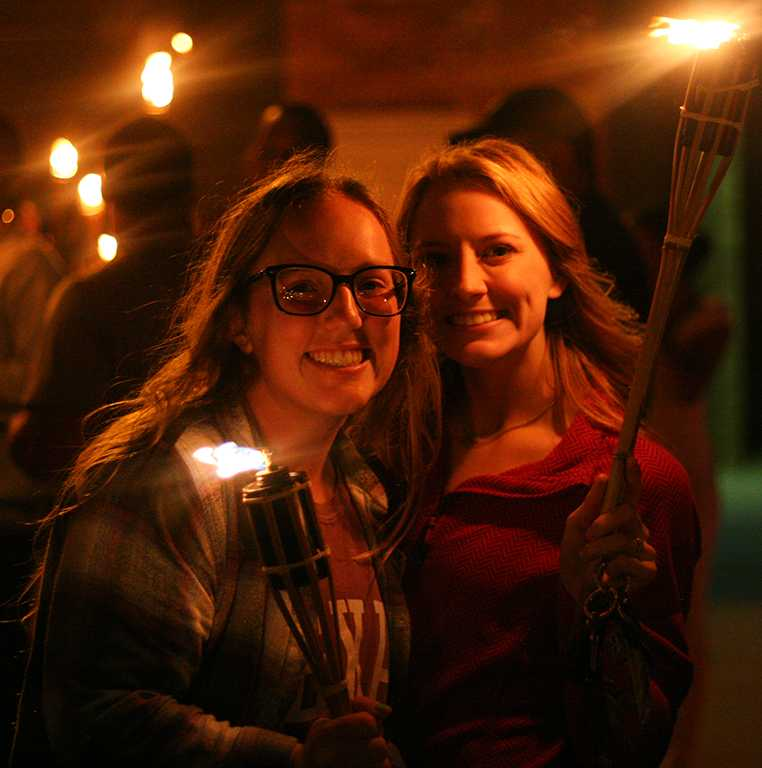 Keelie Ralston, kinesiology junior, and Alicia Mayhugh, kinesiology junior, get ready to start the torchlight parade at MSU on Thursday, Oct. 19, 2017. Photo by Harlie David