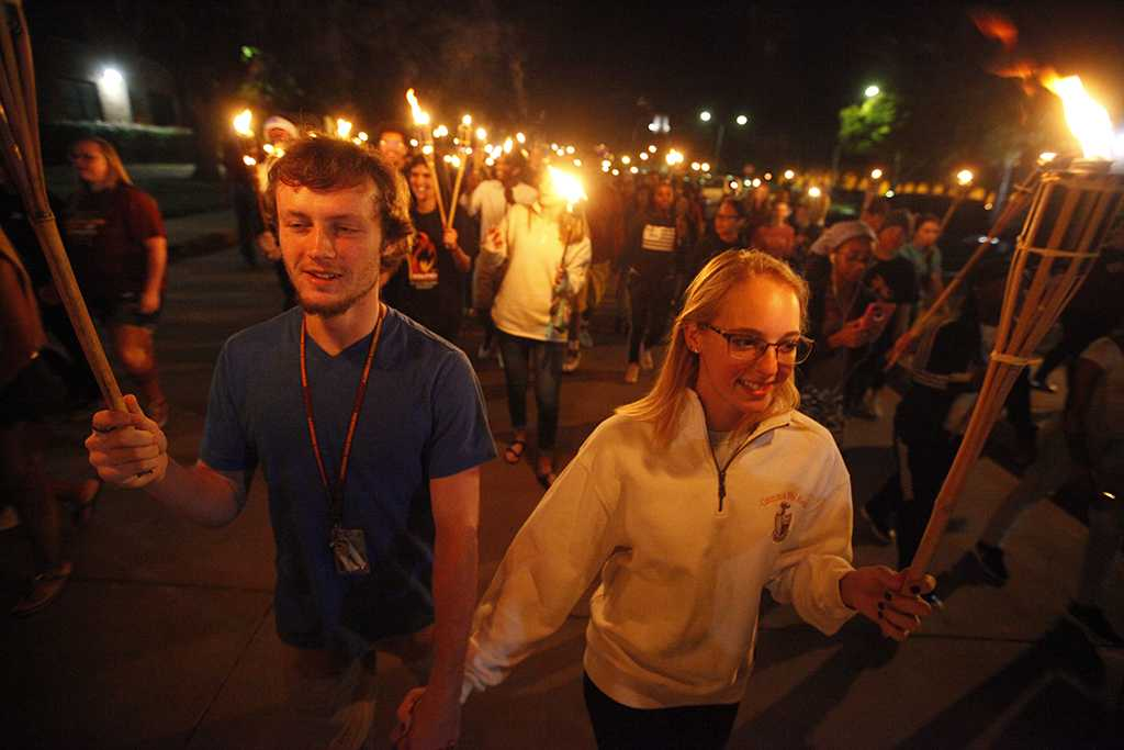 Joshua Luffman, psychology sophomore, and Courtney Lawrence, dental hygiene sophomore, walk in the torch parade. Photo by Bradley Wilson