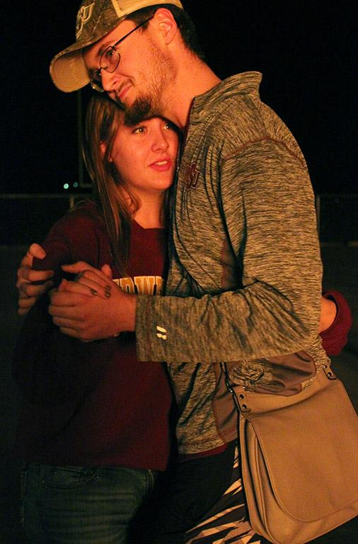 """Carley Bronaugh, psychology freshman, and Jaydon Johnston, math junior, dance together as the Homecoming Bonfire burns in the background and music plays from the stage, Thursday Oct. 19, 2017. """"We've been together for a year and a half. [The Bonfire] I though was really cool, it's both of our first time and it was really awesome,"""" Bronaugh said. Photo by Rachel Johsnon"""