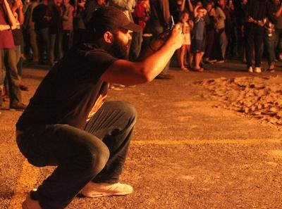 John Smith, psychology junior, gets a picture of the Homecoming Bonfire Thursday, Oct. 19, 2017. Photo by Rachel Johnson