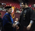 Jesse Rodgers, university president, shakes every students hand as they walk the stage at Midwestern State University fall graduation, Dec. 13, 2014 in Wichita Falls, Texas. Photo by Rachel Johnson