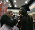 Jessica Gallant, Office of Registrar, helps Omozuwa Omigie, nursing, with her gown at Midwestern State University fall graduation, Dec. 13, 2014 in Wichita Falls, Texas. Photo by Rachel Johnson