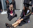 Bevin Pierce, psycology, and Sonia Perez, psycology, sit on the floor while they wait to be moved to the coliseum at Midwestern State University fall graduation, Dec. 13, 2014 in Wichita Falls, Texas. Photo by Rachel Johnson