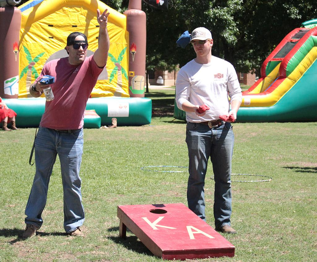Donald James, business finance junior, and Austin Hicks, business managment senior, throwing bean bags at Alpha Phi and Kappa Alpha's First Annual Midwestern Cookout Classic in the Quadrangle on April 30. Photos by Kayla White.