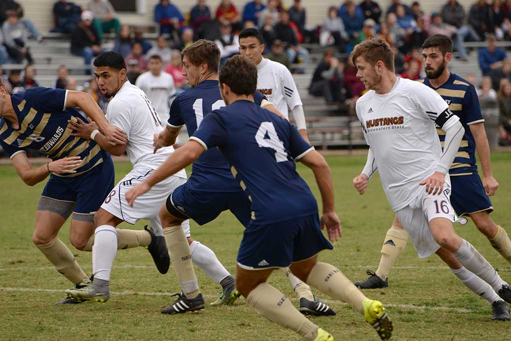 Christopher Mendez and Ross Fitzpatrick fight for control at the Heartland Conference playoff game against St. Edward's. MSU lost 0-2. Photo by Zack Santagate