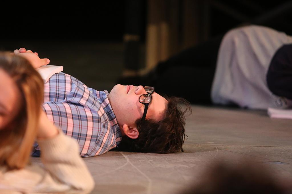Home-school senior Steven Kintner, who plays Tiny Tom, pretends to sleep on the set of Urinetown the Musical on Wednesday, Jan. 19, 2018. Photo by Mekala Conway