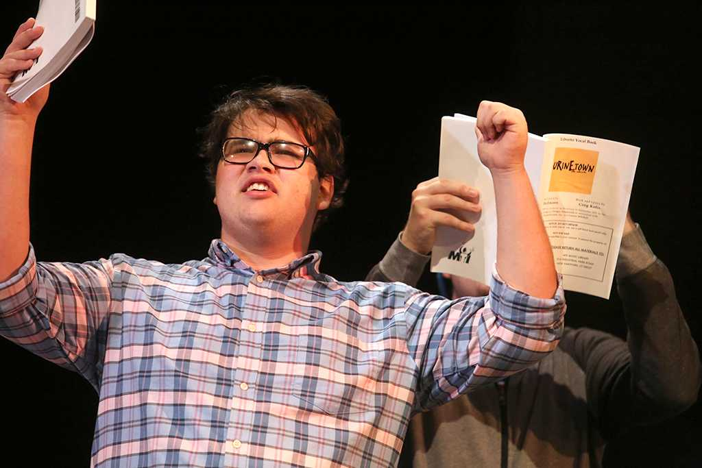 Home-school senior Steven Kintner, who plays Tiny Tom, lifts his arms in frustration at having to pay to use the toilet on the set of Urinetown the Musical on Wednesday, Jan. 19, 2018. Photo by Mekala Conway