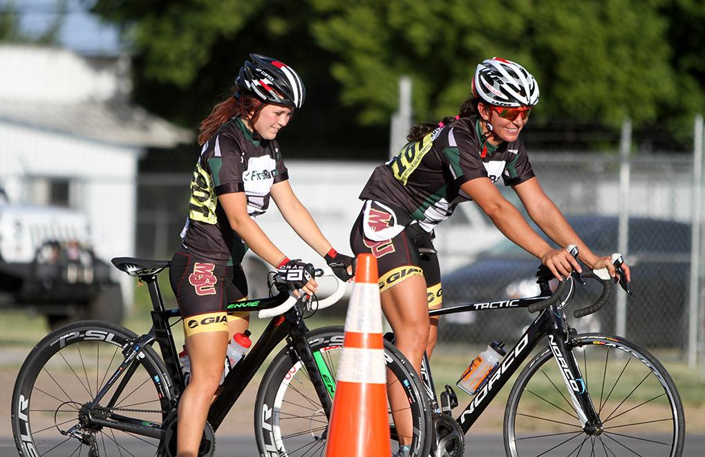 Felicia Westermark-Svanehed and Hannah Ross waits to cross the road at the Hotter 'N Hell men's crit races Friday afternoon.