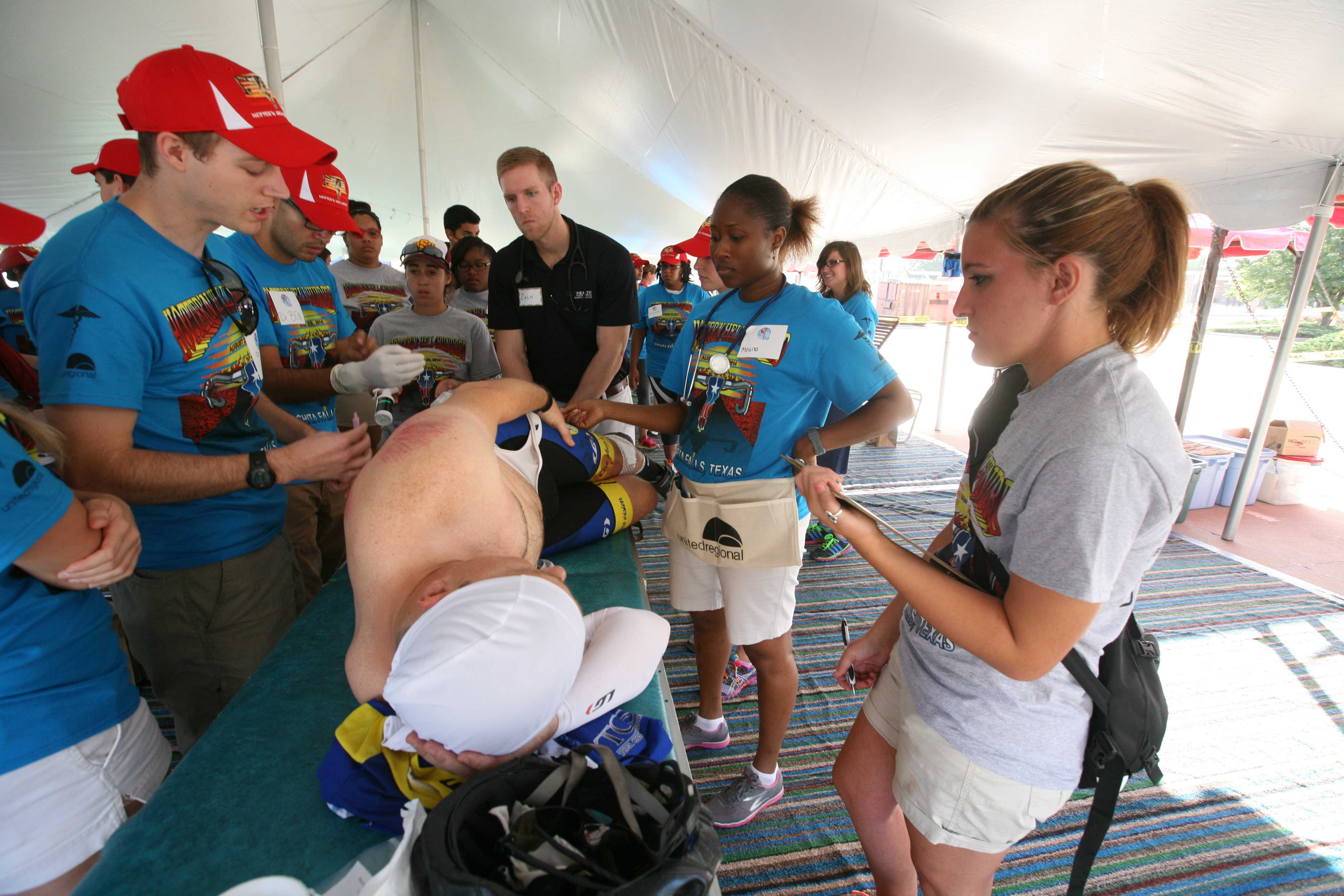 In the medical tent, Moriah Mann (with clipboard), a sophomore in athletic training, works with patient Robert Founds after he fell in the Hotter'N Hell in Wichita Falls, Texas. Photo by Bradley Wilson