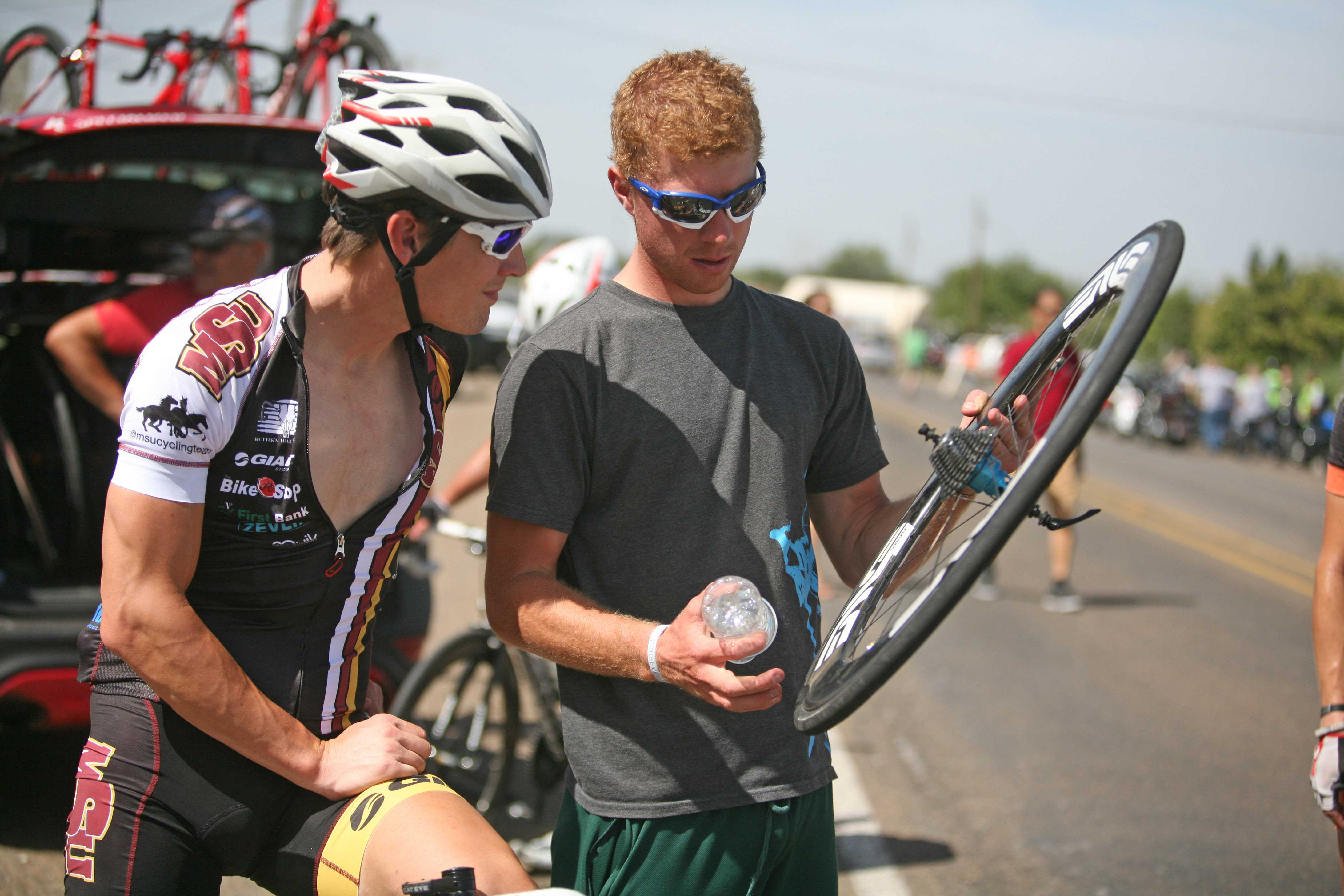 Cory Scott and Sam Croft look over a tire at the finish line of the 100-mile Hotter'N Hell race in Wichita Falls, Texas. Photo by Bradley Wilson