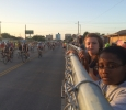 "Macy Pritchett, education sophomore, and Talia Harris, mass communication sophomore, watch the endless stream of racers leave the starting gates as they wait cross the road to deflate and transfer ""Pyro Pete"" to the Hell's Gate rest stop in Burkburnett. Photo by Ethan Metcalf"