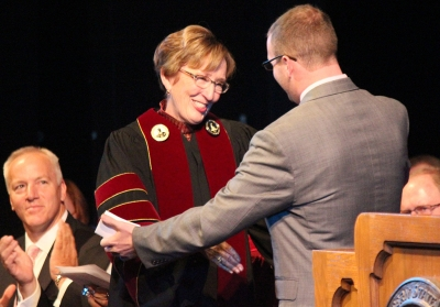 "Jesse Brown, criminal justice senior, hugs Suzanne Shipley after his ""Greetings from the students"" speech about President Suzanne Shipley at the inauguration of Shipley, the eleventh president, held in Fain Fine Arts Auditorium, Dec. 11, 2015. Photo by Rachel Johnson"