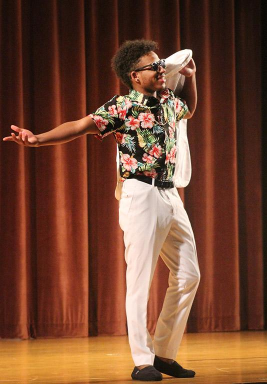 Trevon Charles, biology sophomore, throws his suit jacket over his shoulder while he walks around the stage showing off his outfit during the evening wear portion of the 2017 Mr. and Miss Caribfest Pageant held in Akin Auditorium Sept. 28. Photo by Marissa Daley