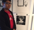 Nevin Diaz, freshman at Wichita Falls High School, posing in front of his print (bottom) in the foyer of Fain Fine Arts, Feb.9. Photo by Conner Wolf.