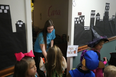 Cara Haitt, nursing freshman, passes out candy while the kids of YMCA trick or treat in Killingsworth Residence Hall at Midwestern State University. Photo by Justin Marquart