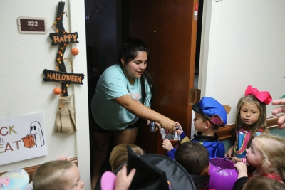 Clarissa Rios, dental hygiene freshman, passes out candy while the kids of YMCA trick or treat in Killingsworth Residence Hall at Midwestern State University. Photo by Justin Marquart