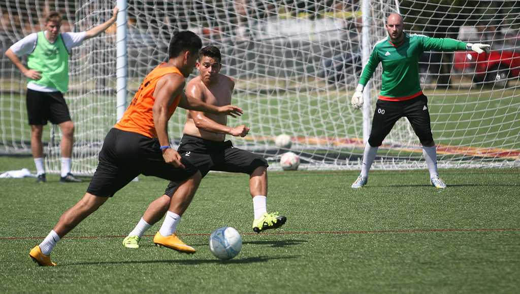 Jeffrey Palomarez, sophomore, fights for the ball from Antonio Hernandez, education senior, when the soccer players gathered the week before official practice began to run plays on the new turf field. Earlier in the week, coaches had recorded temperatures approaching 150˚F on the turf field. Photo by Dylan Pembroke.
