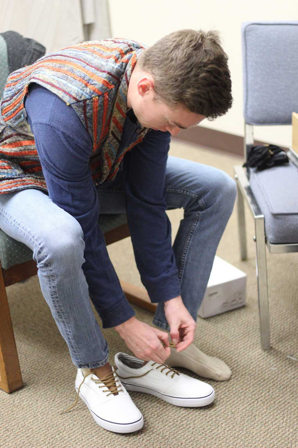 "Sam Mitchell tries on shoes for his costume of ""Bobby"" at the final fittings on Feb. 14 Photo by: Avery Whaite"