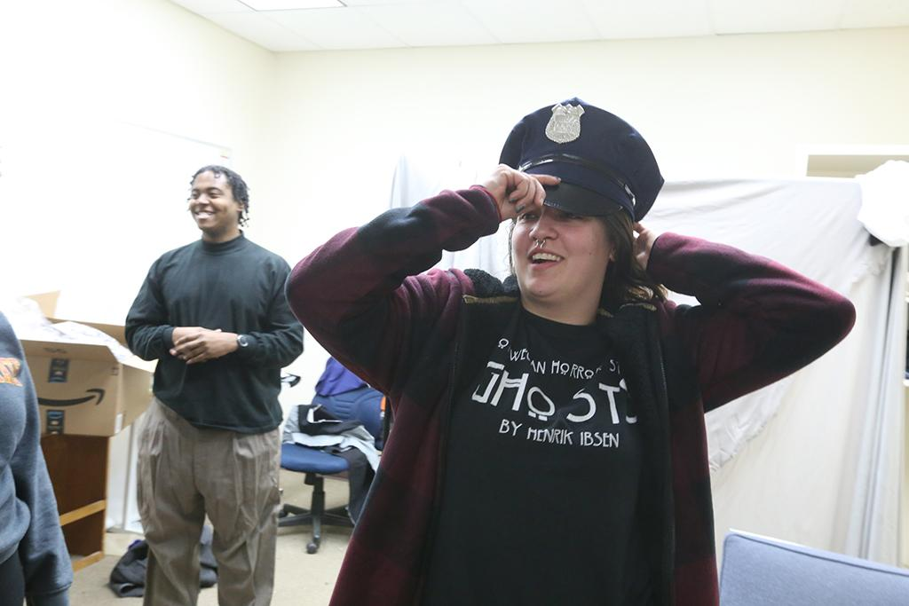 "Ellanor Collins tries on her police officer's hat in preparation for ""Urinetown"" that opens Feb. 22 at Midwestern State University. Photo by Bradley Wilson"