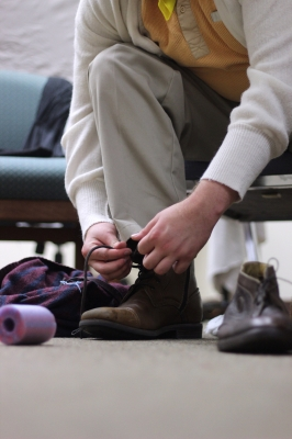 Clay Tabor laces his boots on to see if they fit for the Midwestern State Prodcution of Urinetown. Photo by: Leo Gonzalez.