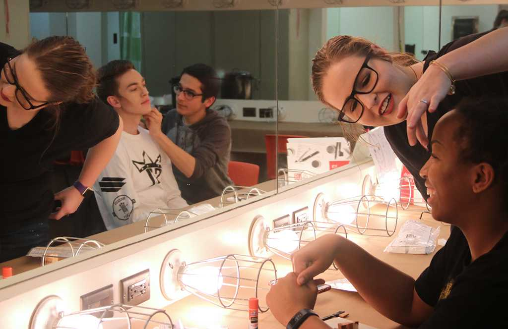 Urinetown cast members practice applying the character's make-up design for the first time in the dressing room on Friday, Feb.16, 2018. Photo by Joanne Ortega