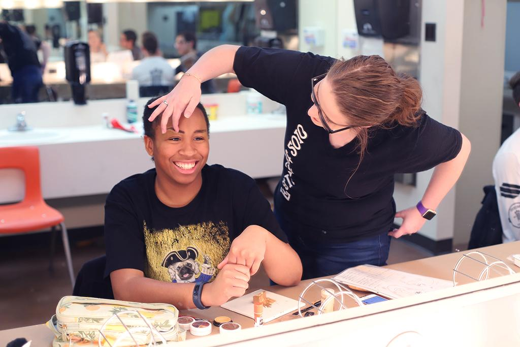 Abby Allen, theater education sophomore, helps Nicole Smalls, Penelope Pennywise and theater performance sophomore, draw on her eyebrows for Urinetown in the dressing room on Friday, Feb. 16, 2018. Photo by Sarah Graves
