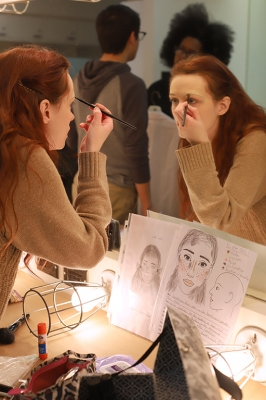 As a way to practice the make-up design for her character Little Sally, Kalli Root, english junior, looks at the sheets as reference while she does her makeup for the first time in the dressing room on Friday, Feb.16, 2018. Photo by Joanne Ortega