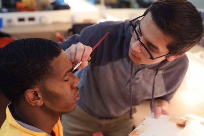 Kendall Jones learns how to apply his makeup for Urinetown from Christopher Cruz, head of makeup and Mr. McQueen, in the dressing room on Feb. 16, 2018. Photo by Sarah Graves
