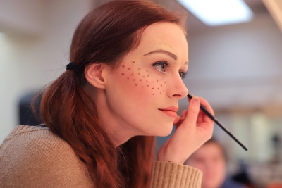 Kalli Root applies makeup for Urinetown in the dressing room on Feb. 16, 2018. Photo by Sarah Graves