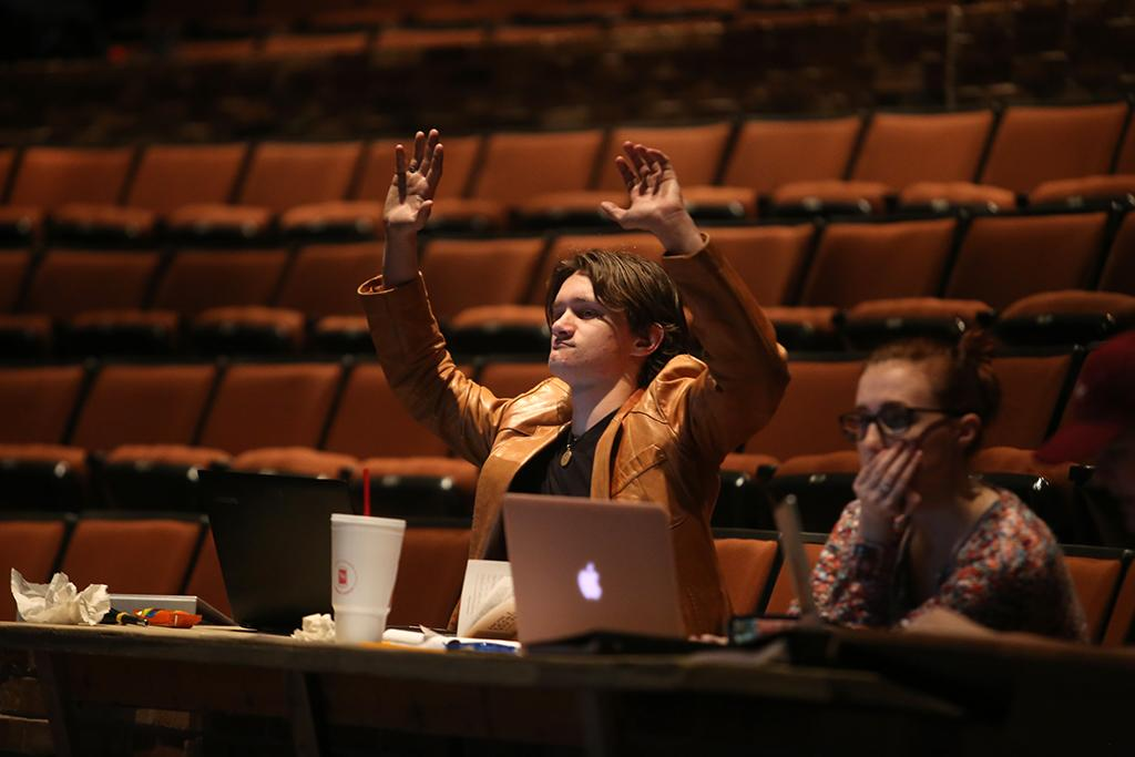 Ron Harle joins the cast in waving at rehearsal for the Midwestern State University production of Urinetown. Photo by Bradley Wilson