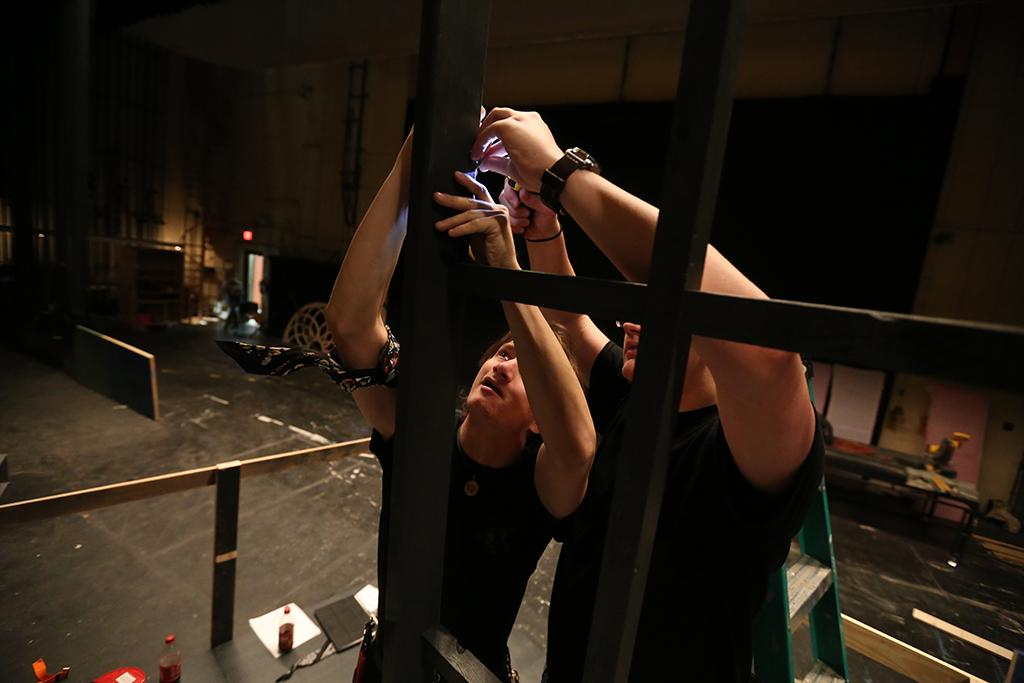 "Ron Harle and Seth Angelino, assistant master carpenter, work to get the set for ""Urinetown"" ready Jan. 30. Crew members worked from 1-5 p.m. every day and some evenings and weekends. Photo by Bradley Wilson"