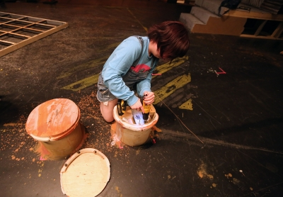 "Shae Dorsman helps to take down the set of ""Urinetown."" Photo by Bradley Wilson"