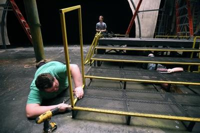 "Dean Hart helps to take down the set of ""Urinetown."" Photo by Bradley Wilson"