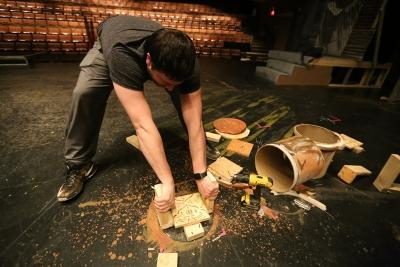 "Ben Ashton helps to destroy some of the set plumbing while taking down the set of ""Urinetown."" Photo by Bradley Wilson"