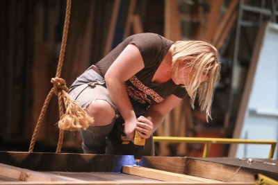 "Emily Burns helps to take down the set of ""Urinetown."" Photo by Bradley Wilson"