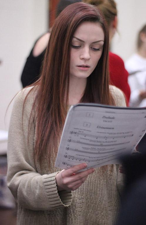 Kalli Root, English junior, practices one of the songs as one of the sopranos during the first rehearsal of UrineTown. Photo by Rachel Johnson
