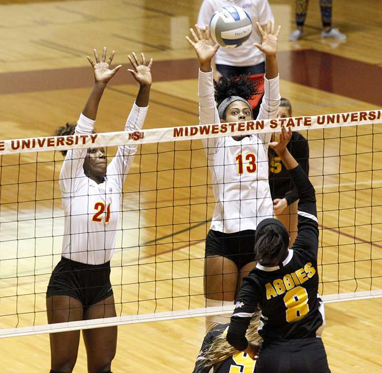 Raven Presley, mechanical engineering freshman, and Aerielle Edwards, applied arts & aciences senior, jump up to block the incoming ball from a Cameron University opponent during the volleyball game in D.L. Ligon Coliseum on Nov. 9, 2017. Photo by Harlie David
