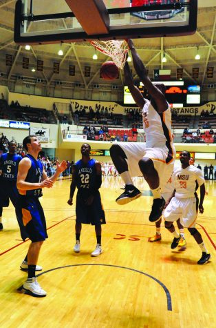 Air time: Junior forward Anthony Harris dunks against Angelo State.   Photo by Hannah Hofmann