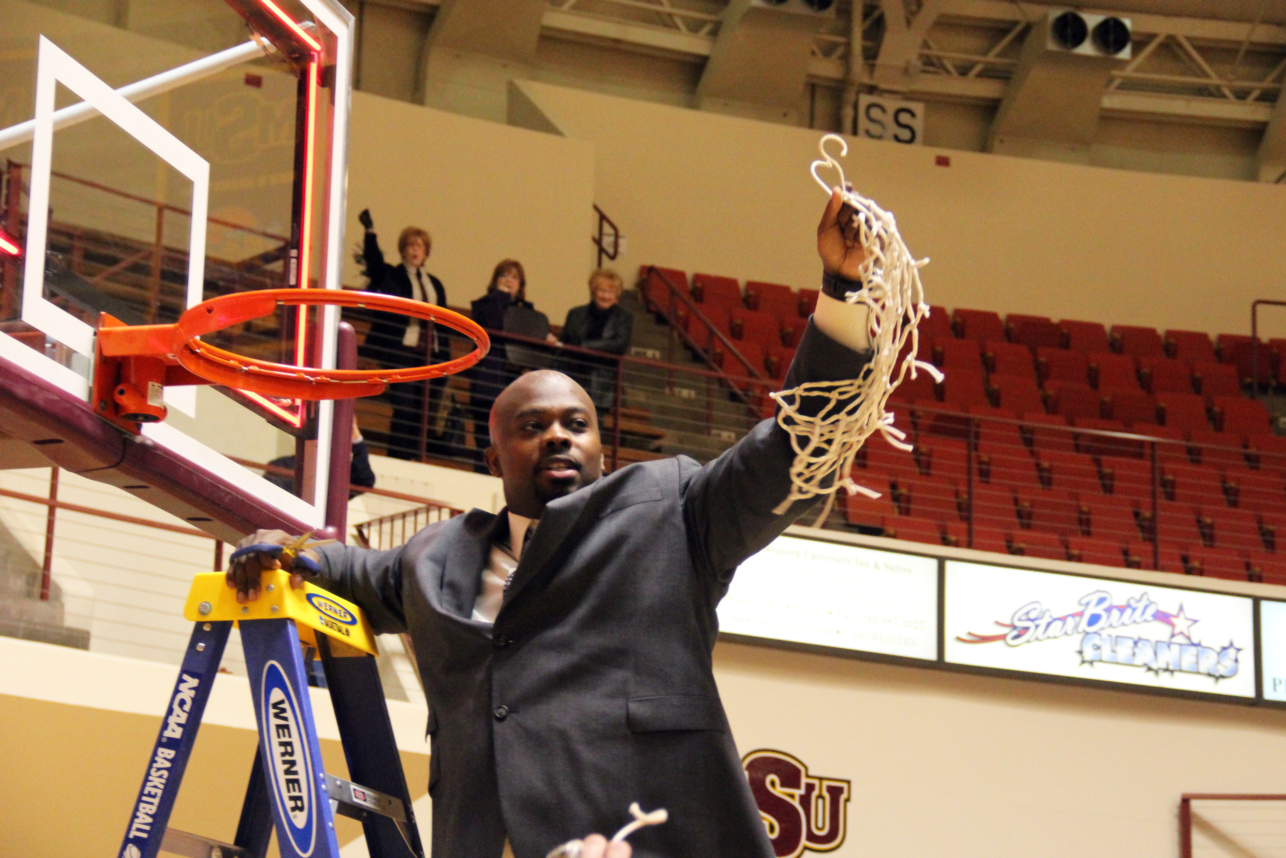 Head Coach, Nelson Haggerty, waves the net after the Mustangs win their second consecutive Lone Star Conference Championship in 2013.
