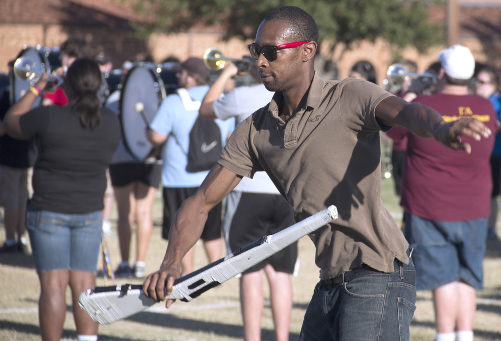 Jammal Cook Reyes, color guard director, goes through the rifle routine during band practice Tuesday, Sept. 3 on the football field.